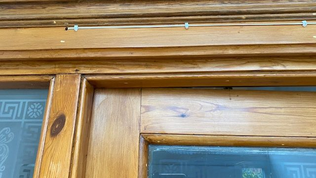 Deurbeldraad met kabelclips op houten deurframe, vooraanzicht.