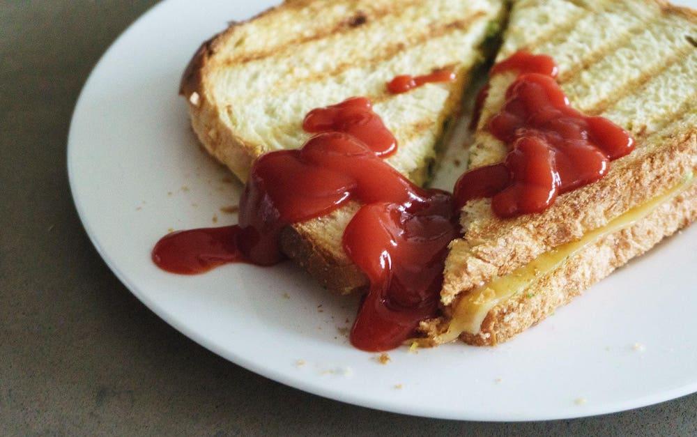 tosti met ketchup op een wit bord
