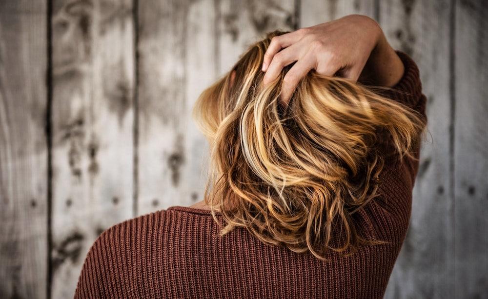 vrouw met hand in blond haar van achteren