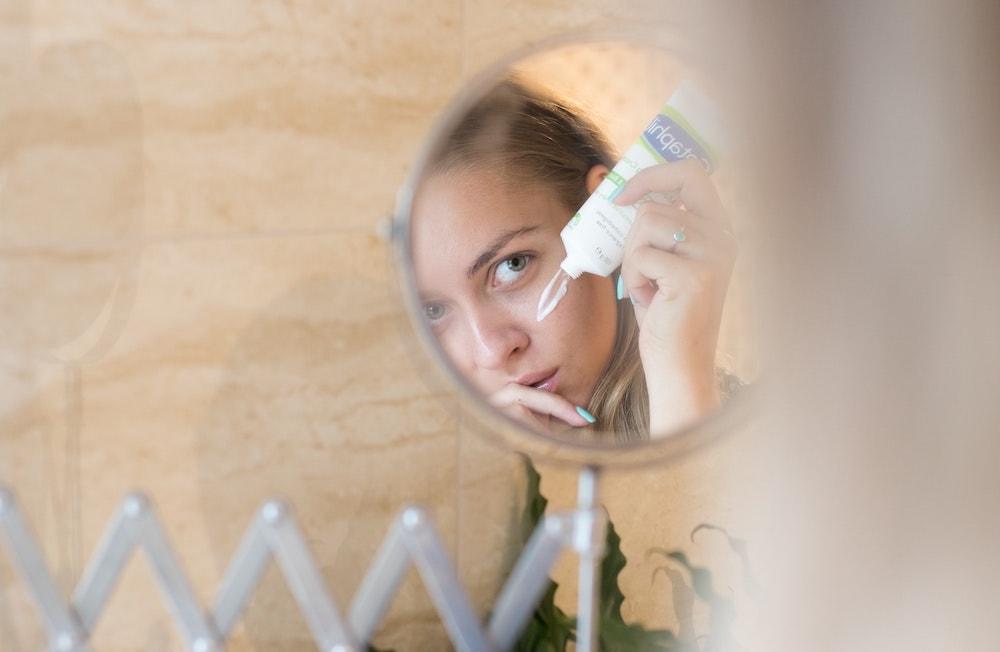 vrouw smeert creme uit tube op gezicht in kleine spiegel