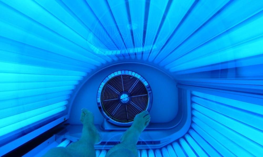 zonnebank van binnen met lampen aan en benen in beeld