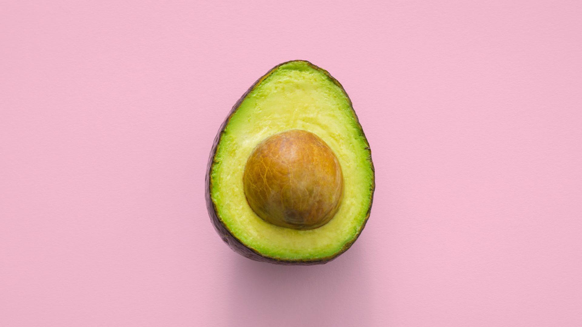 Halve avocado op roze achtergrond, bovenaanzicht