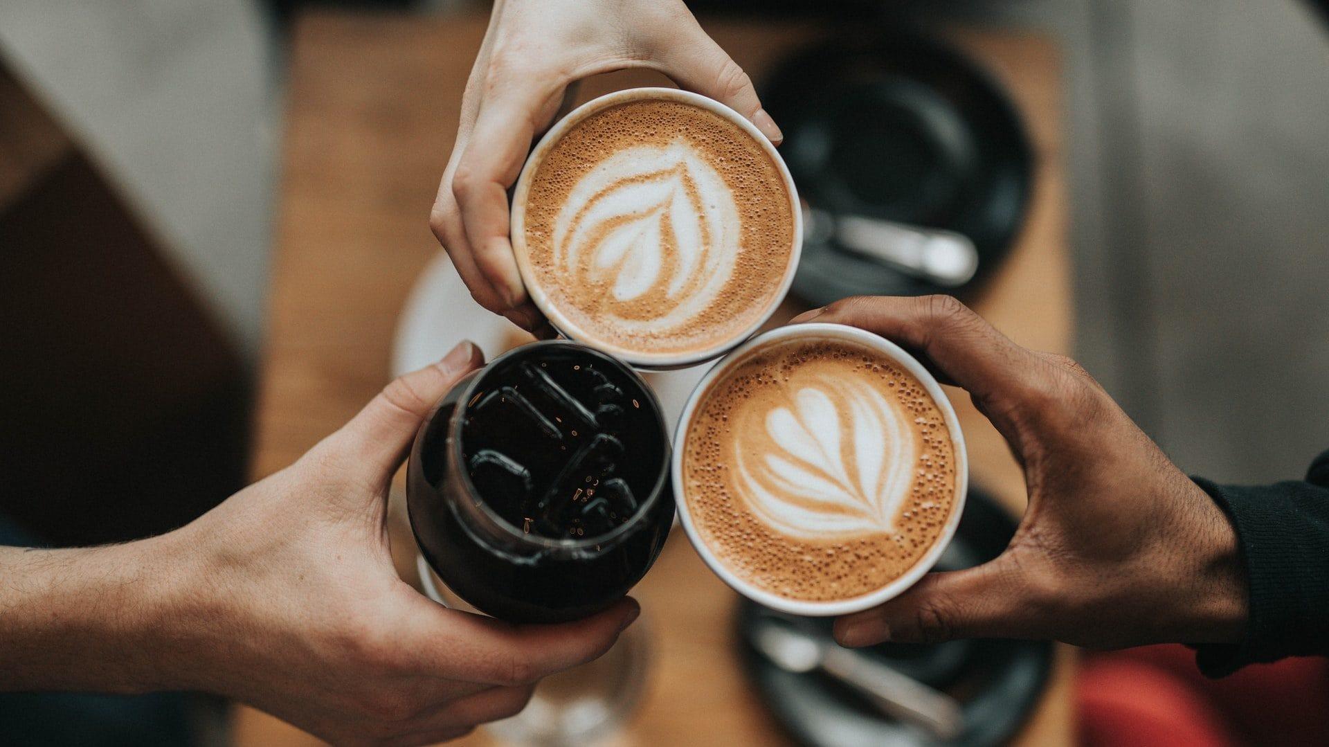 Drie handen met een kopje koffie, bovenaanzicht