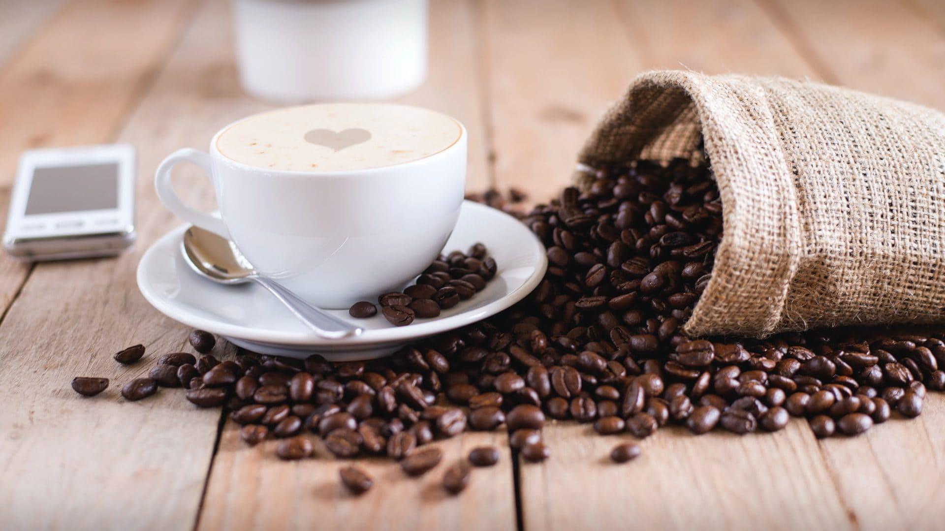 Kop koffie met zak bonen ernaast, op houten ondergrond. Vooraanzicht