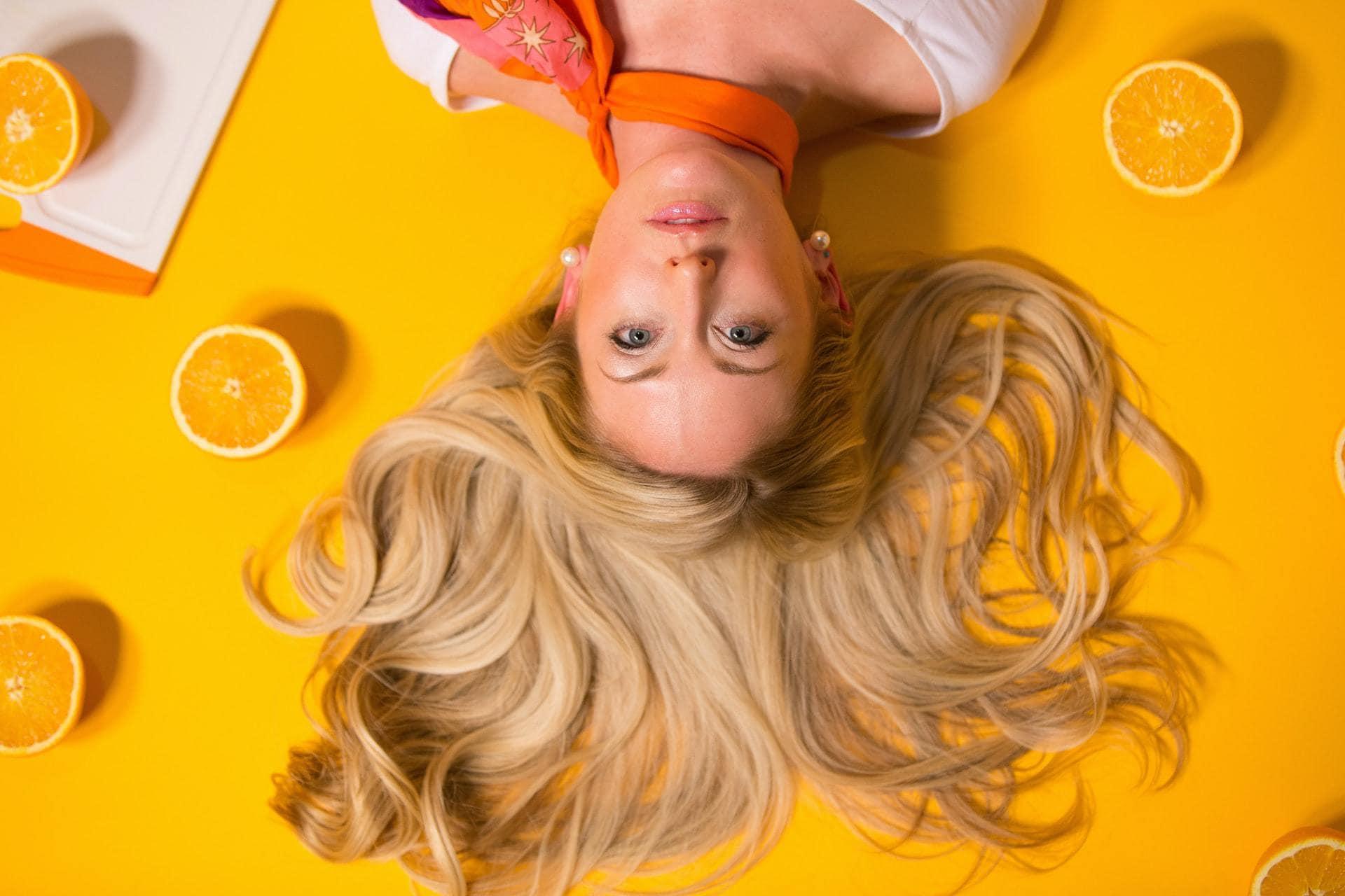 Vrouw met lang haar op gele achtergond met sinaasappels