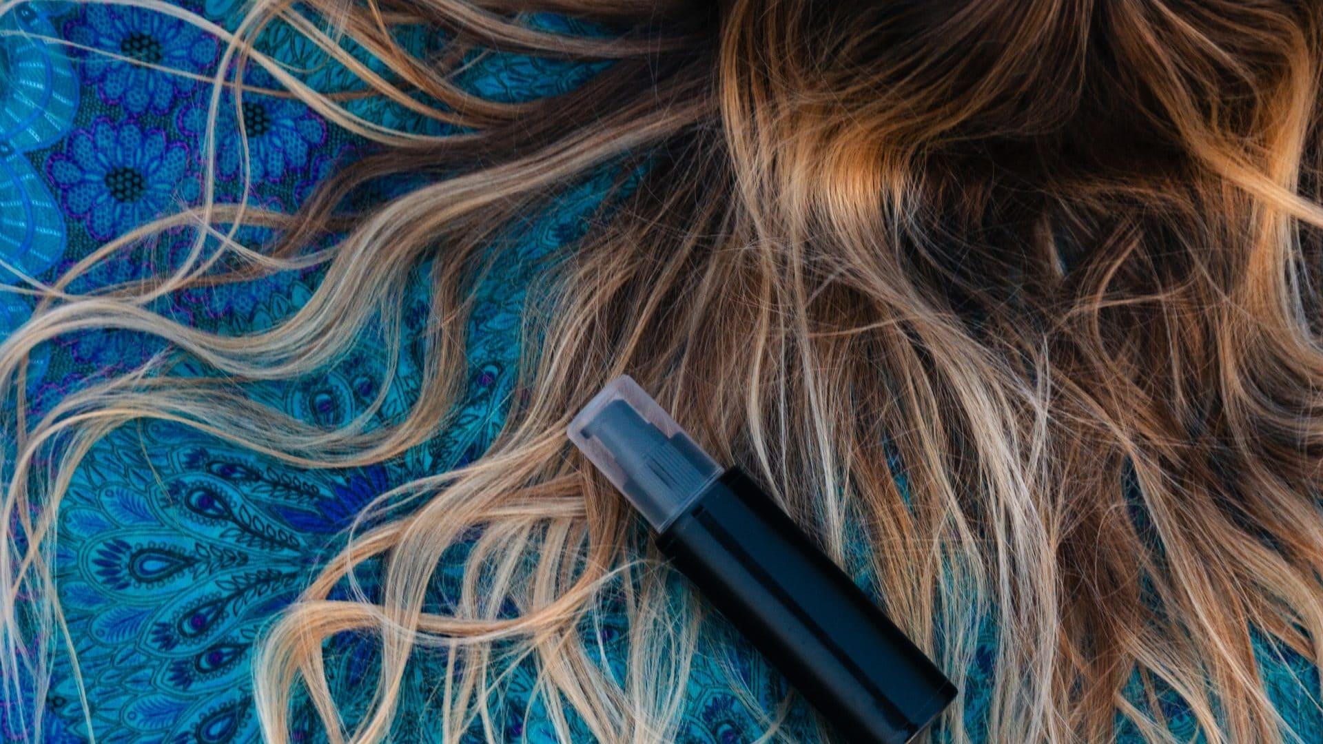 Haar op blauwe achtergrond met zwart flesje