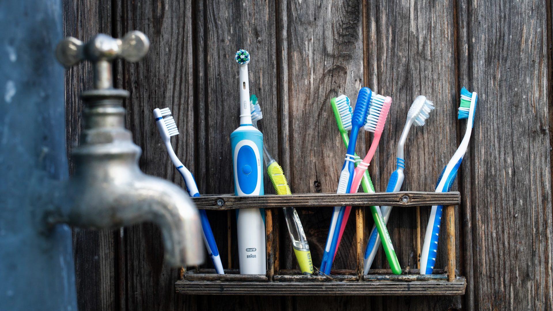 Tandborstels in tandenborstelhouder, met kraan op de voorgrond. Vooraanzicht