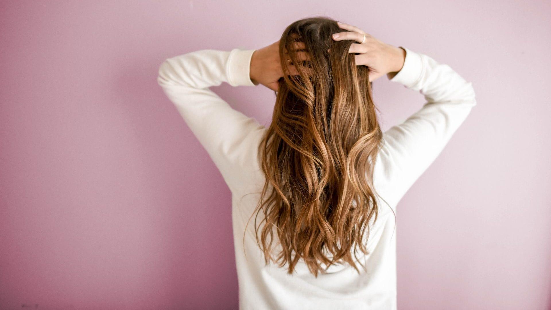 Vrouw met lang haar achterzijde, op roze achtergrond
