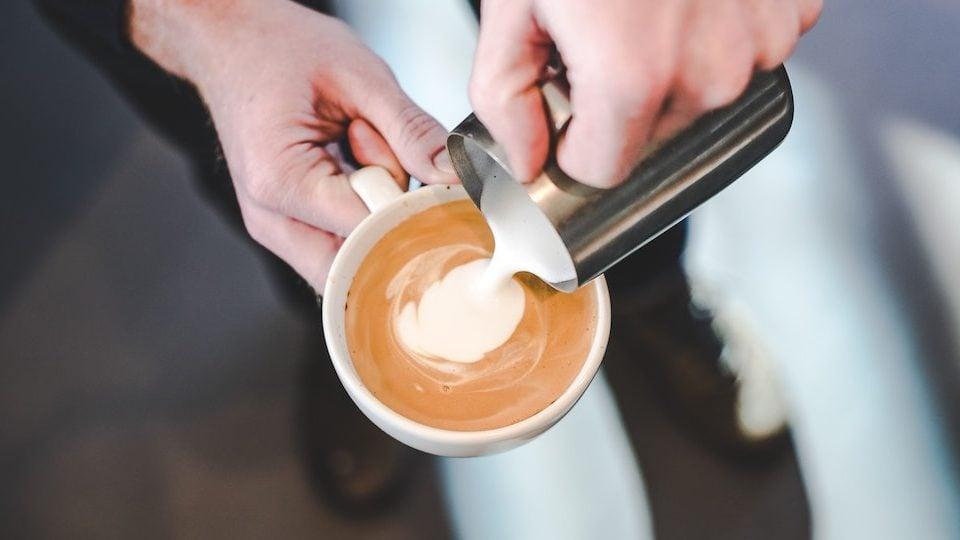 man schenkt geschuimde melk in koffie