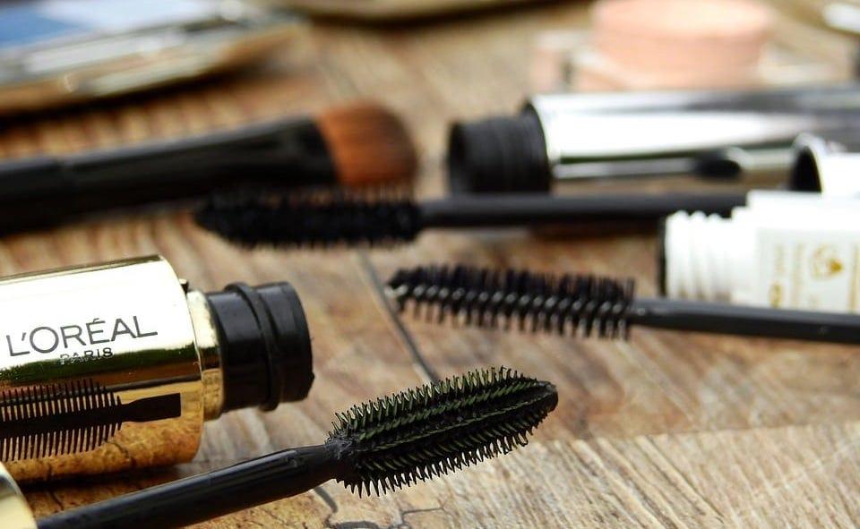 mascaraflesjes en borsteltjes op houten tafel