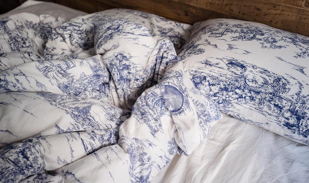 onopgemaakt bed met dekbed zichtbaar