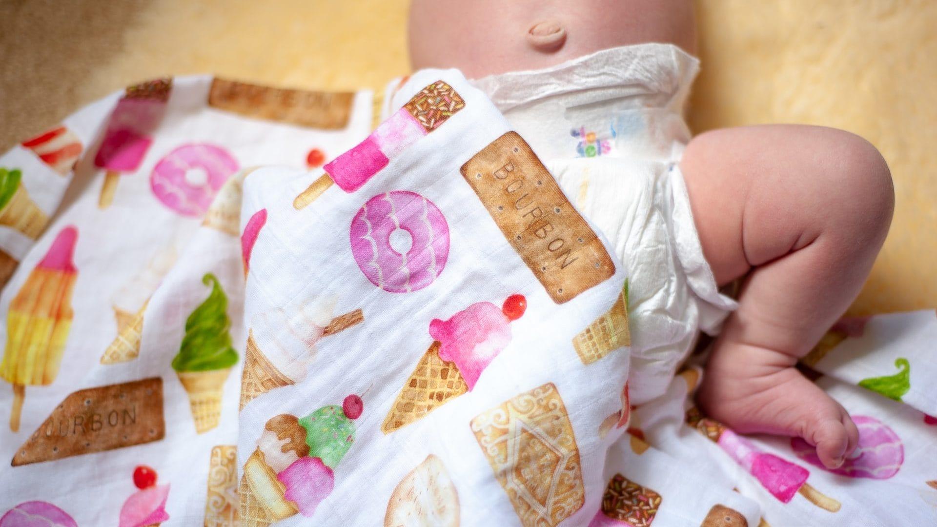 Onderkant van een baby met een doek met koekjes en ijsjes, op gele achtergrond. Bovenaanzicht