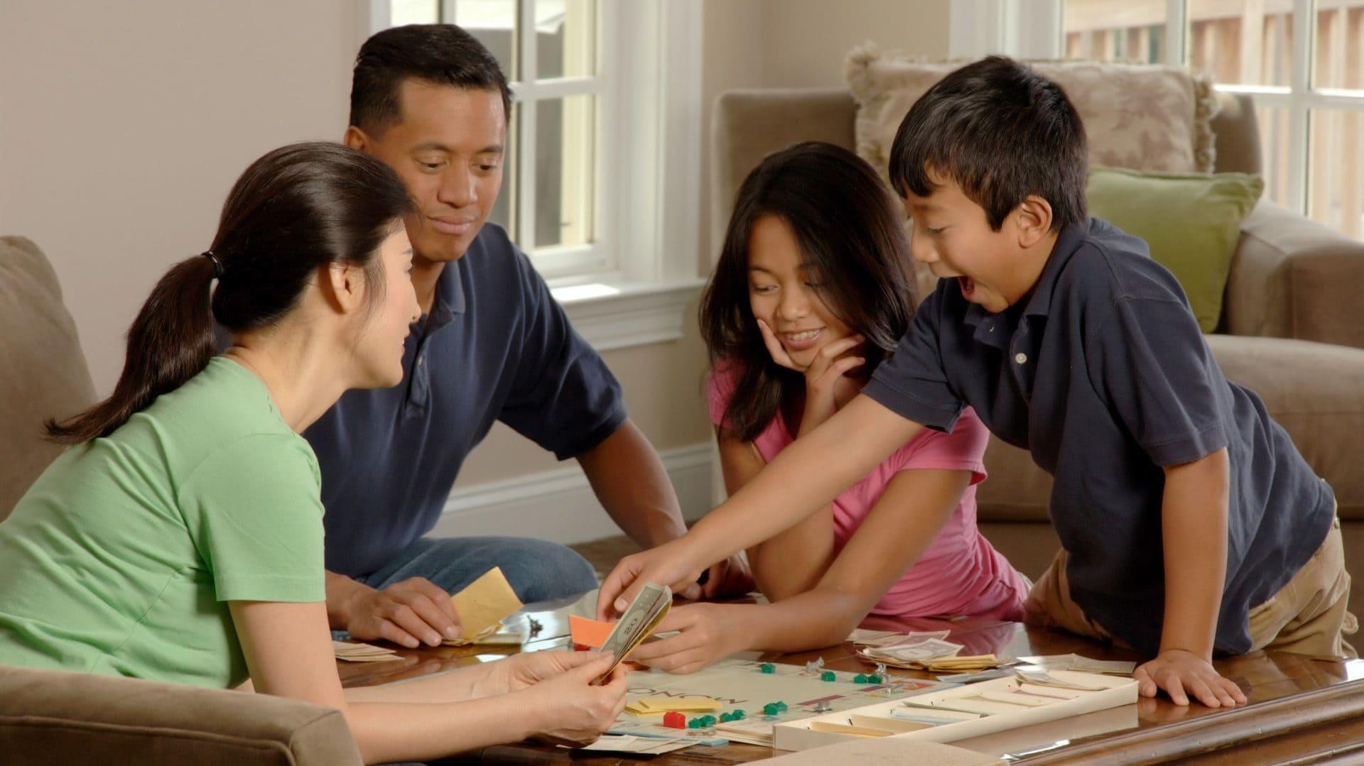Familie speelt een bordspel op de koffietafel
