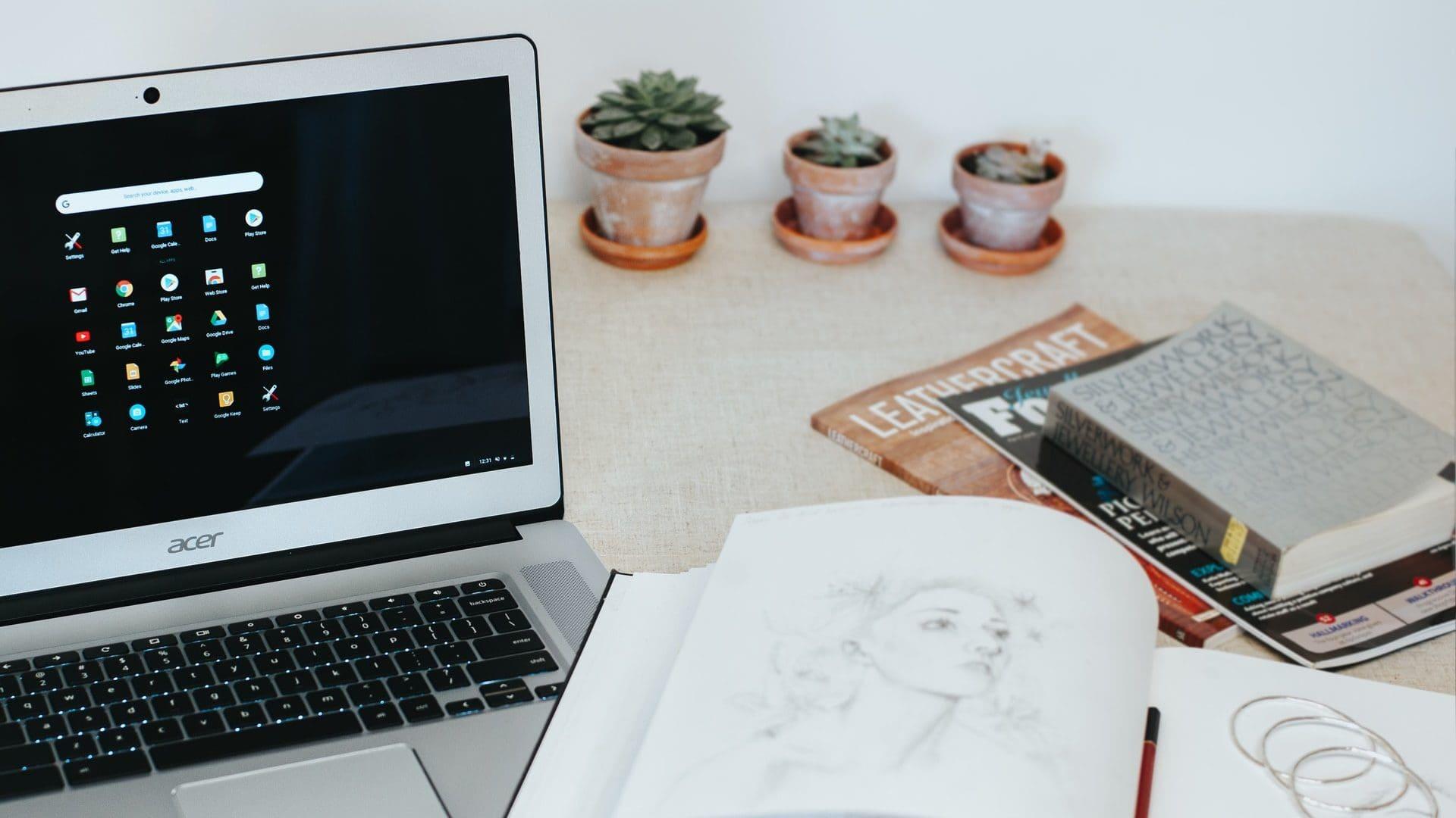 Chromebook op tafel, met boeken en plantjes op de achtergrond.