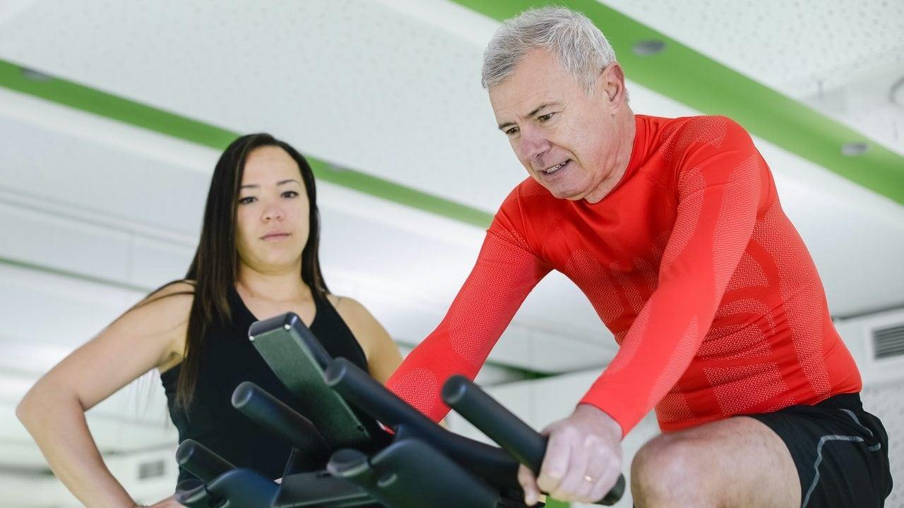 Man met oranje shirt op hometrainer, met vrouw ernaast met lang, zwart haar. Zij-aanzicht