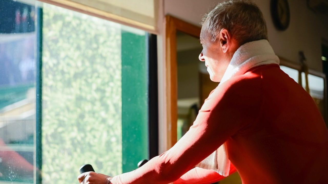 Man met oranje shirt op hometrainer, zij-aanzicht