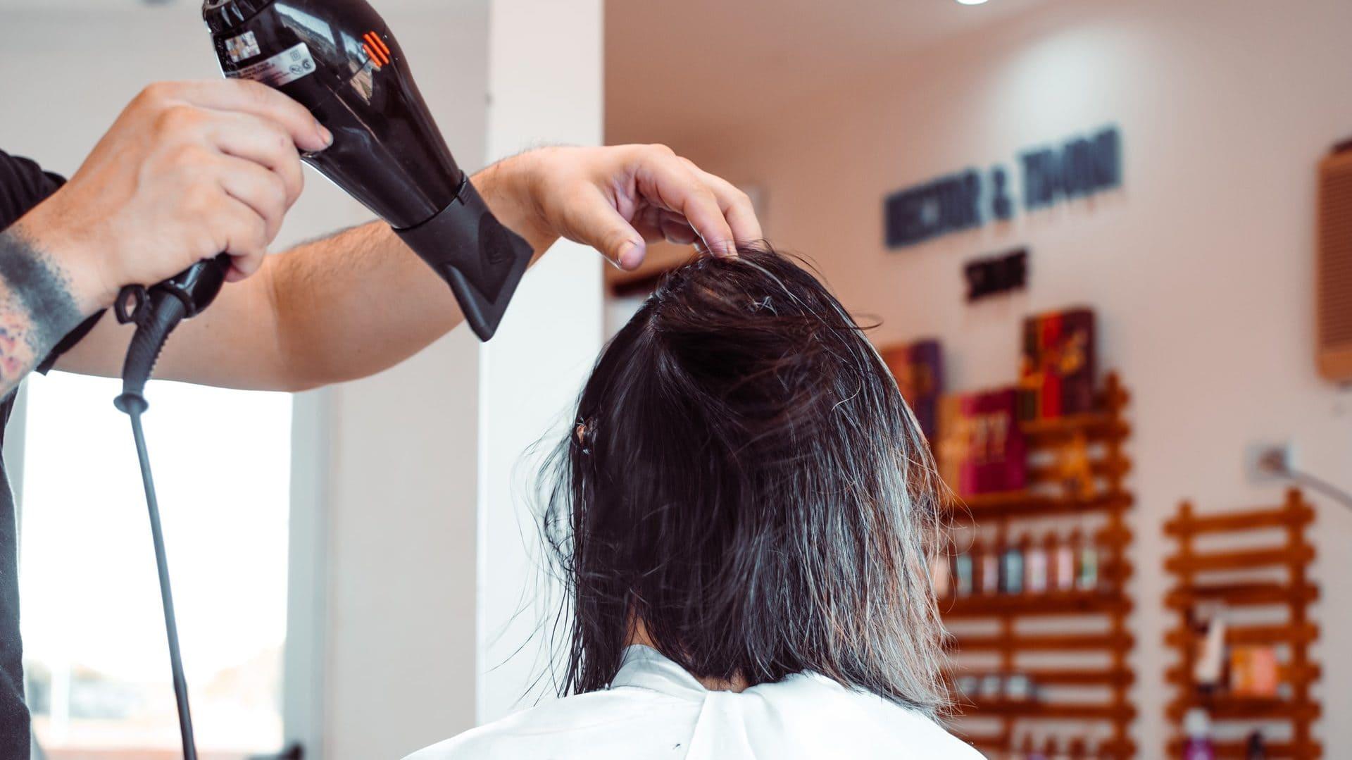 Bij de kapper, vrouw met donker haar, föhn. Achterzijde.