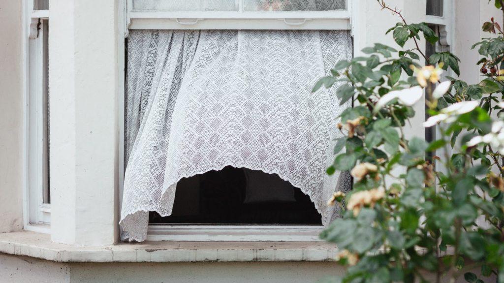 Open raam met wit gordijn