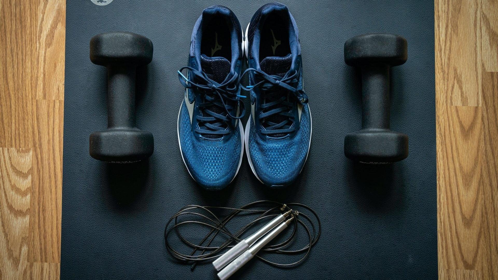 Sportschoenen, gewichtjes en springtouw. Bovenaanzicht