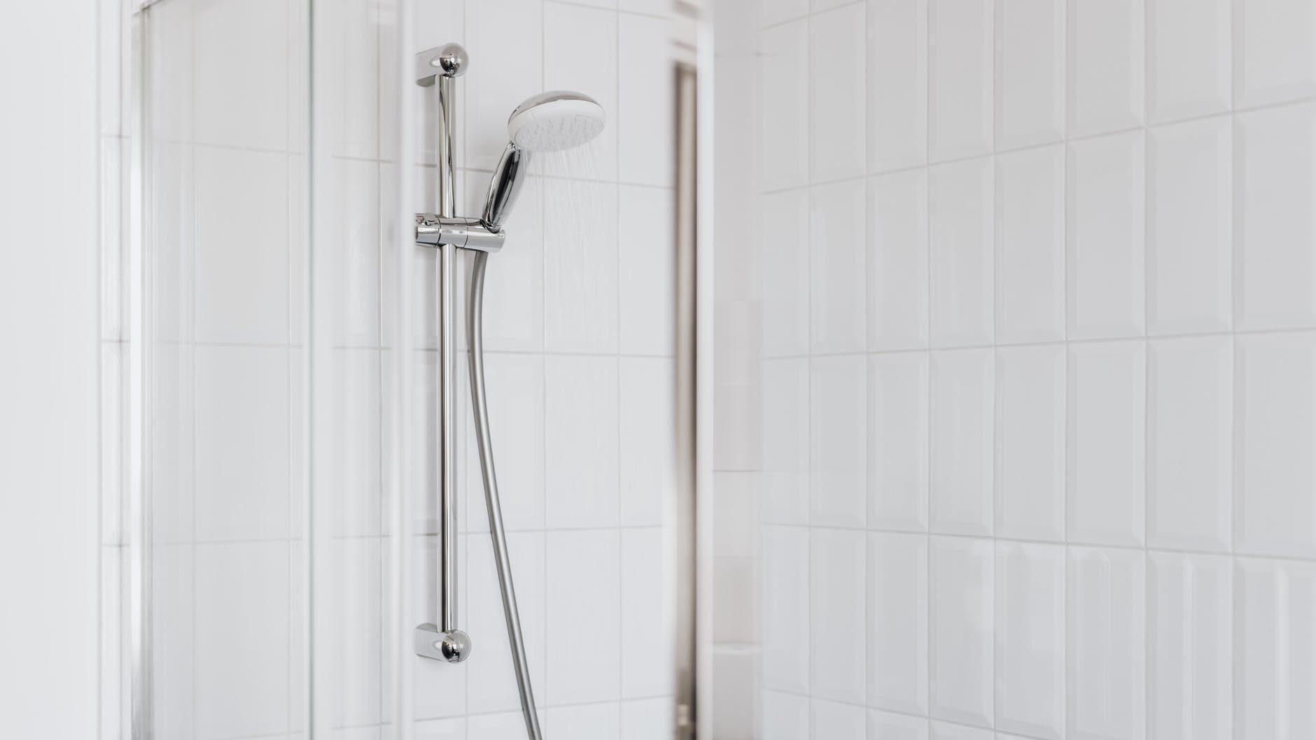 handdouchekop aan stang in badkamer