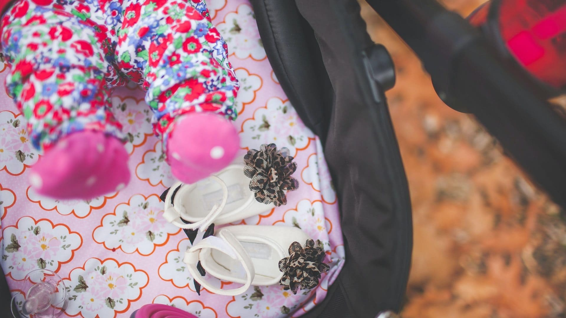 Kinderwagen met baby erin, roze schoentjes en witte schoentjes. Bovenaanzicht
