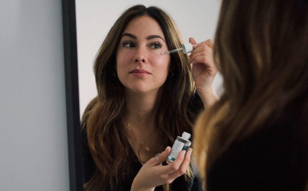 Vrouw die voor de spiegel een serum aanbrengt