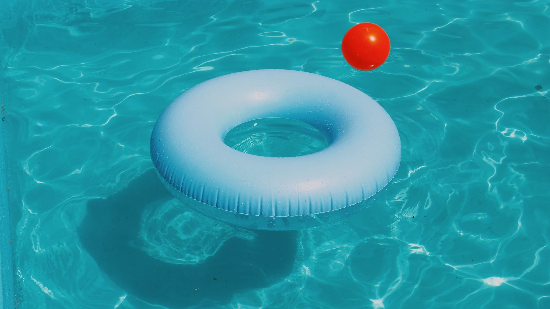 Opblaasbare band in water, met rode bal. Bovenaanzicht