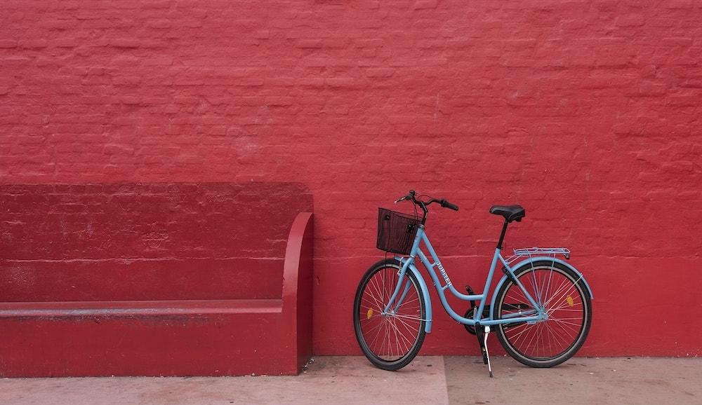 blauwe mamafiets tegen rode muur