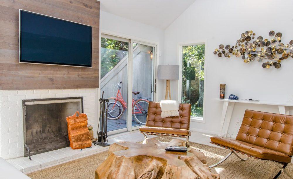 Huiskamer met tv aan de muur, boven de open haard