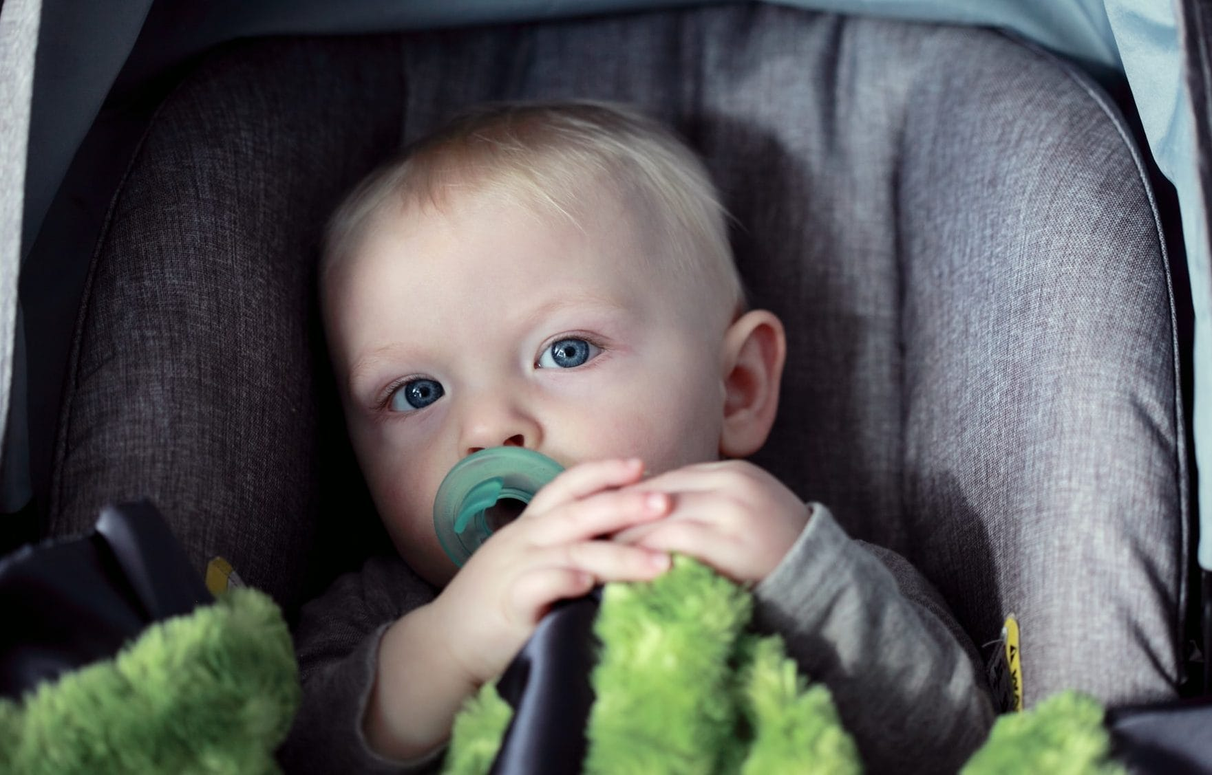 Kindje met groen truitje in autostoel, vooraanzicht