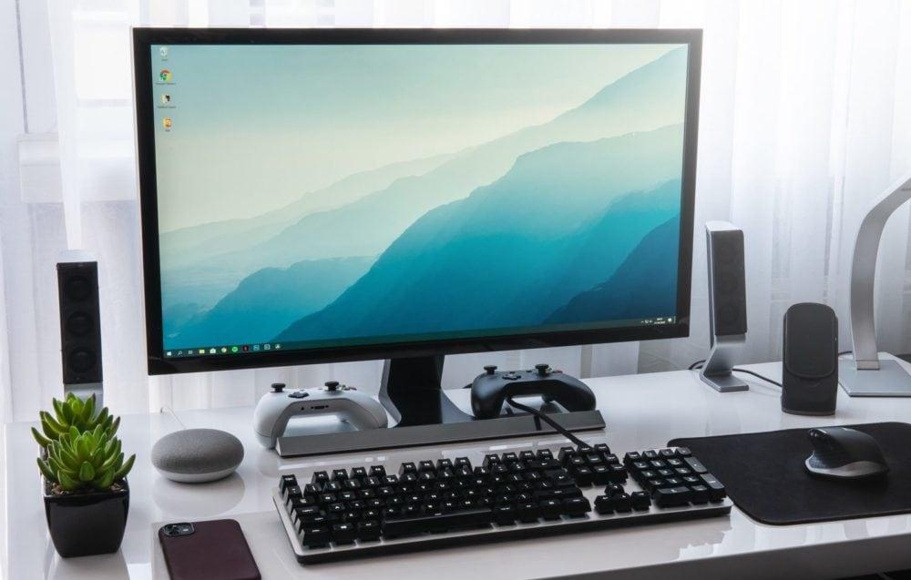 Desktop computer met speakers, toetsenbord, muis en muismat, plantje. Vooraanzicht