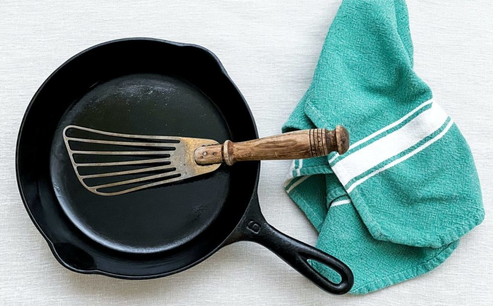 Gietijzeren koekenpan met groene handdoek en spatel. Bovenaanzicht