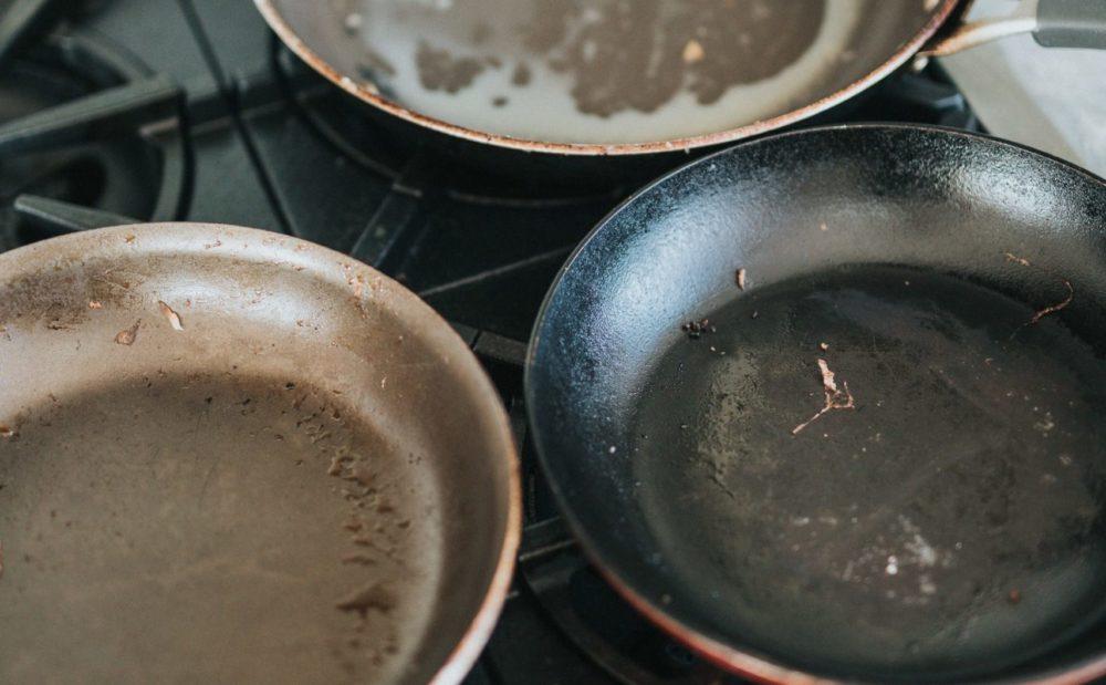 Drie koekenpannen op gasfornuis, aangekoekt. Bovenaanzicht