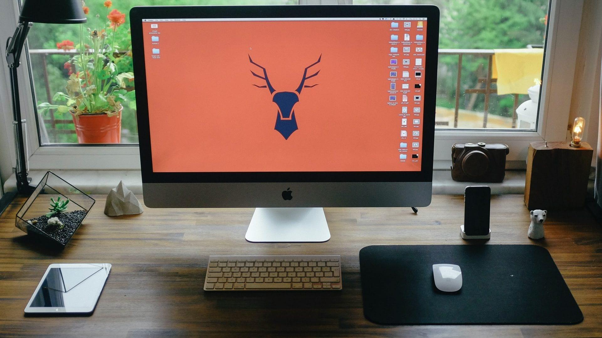 iMac op houten bureau bij raam