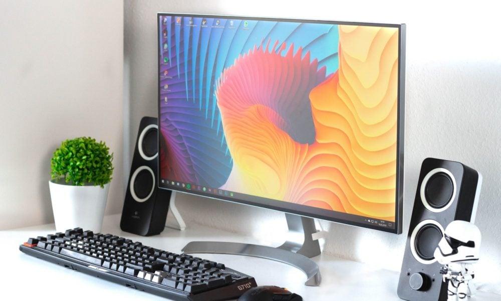 Monitor met toetsenbord, speakers en plantje, schuin vooraanzicht