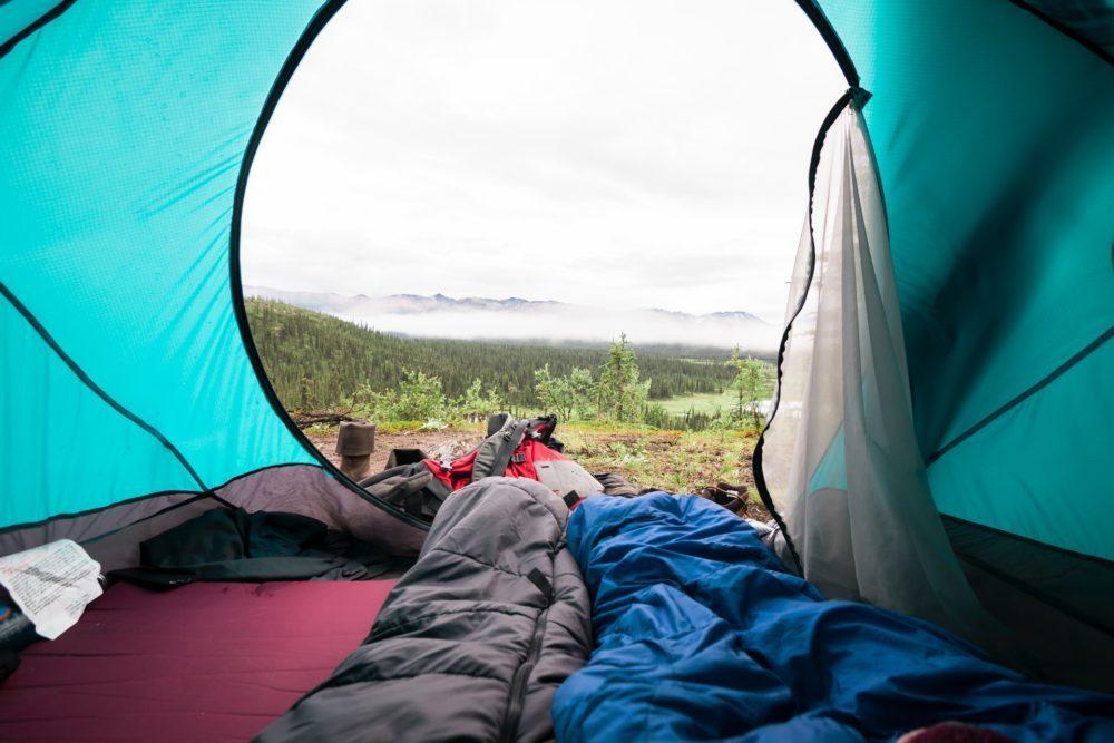 Twee slaapzakken in tent met uitzicht op de bergen