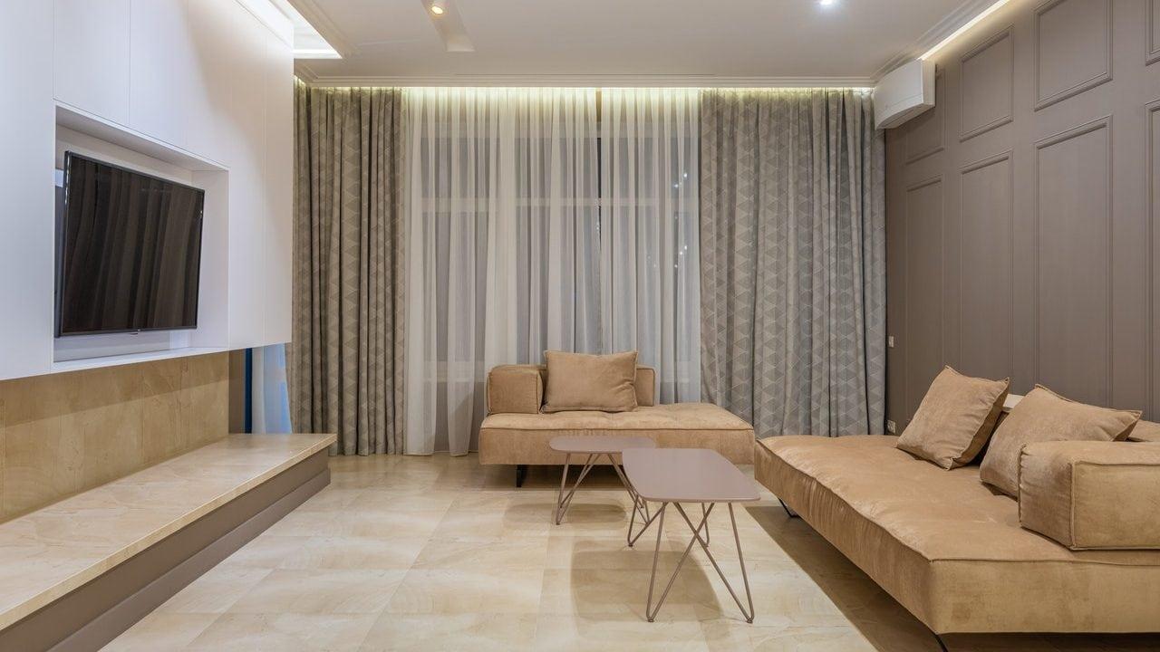 Tv aan de muur in de huiskamer, lichtbruine lederen bank met crèmekleurige tegels en twee tafels