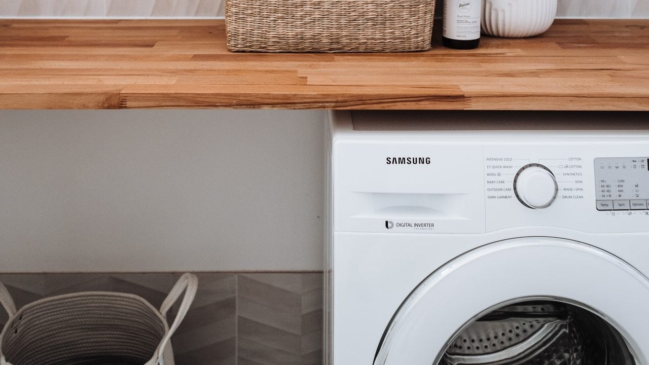 Samsung wasmachine onder een houten tafelblad