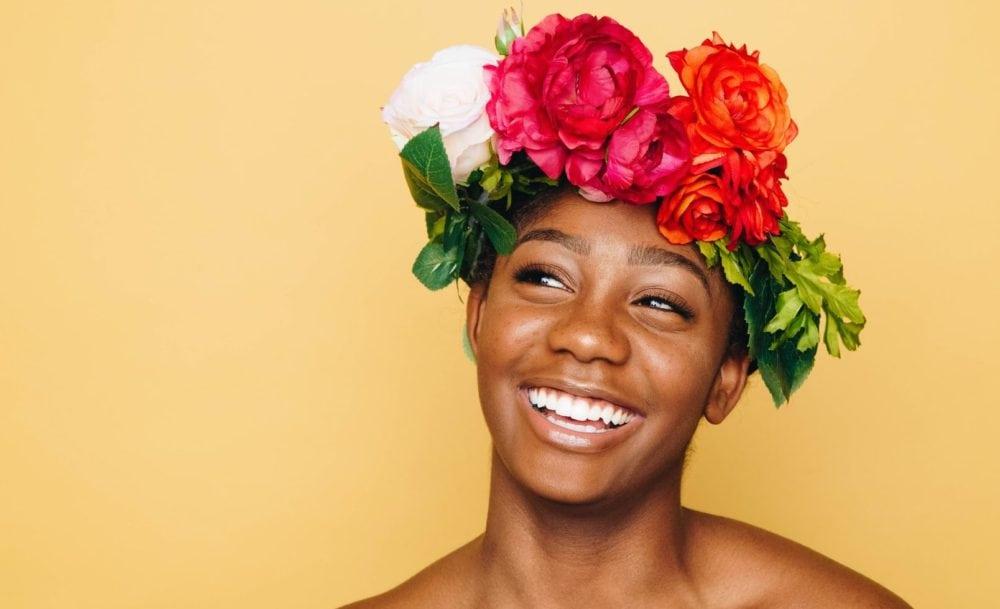 Vrouw met brede lach, witte tanden en bloemenkrans op hoofd. Op gele achtergrond.