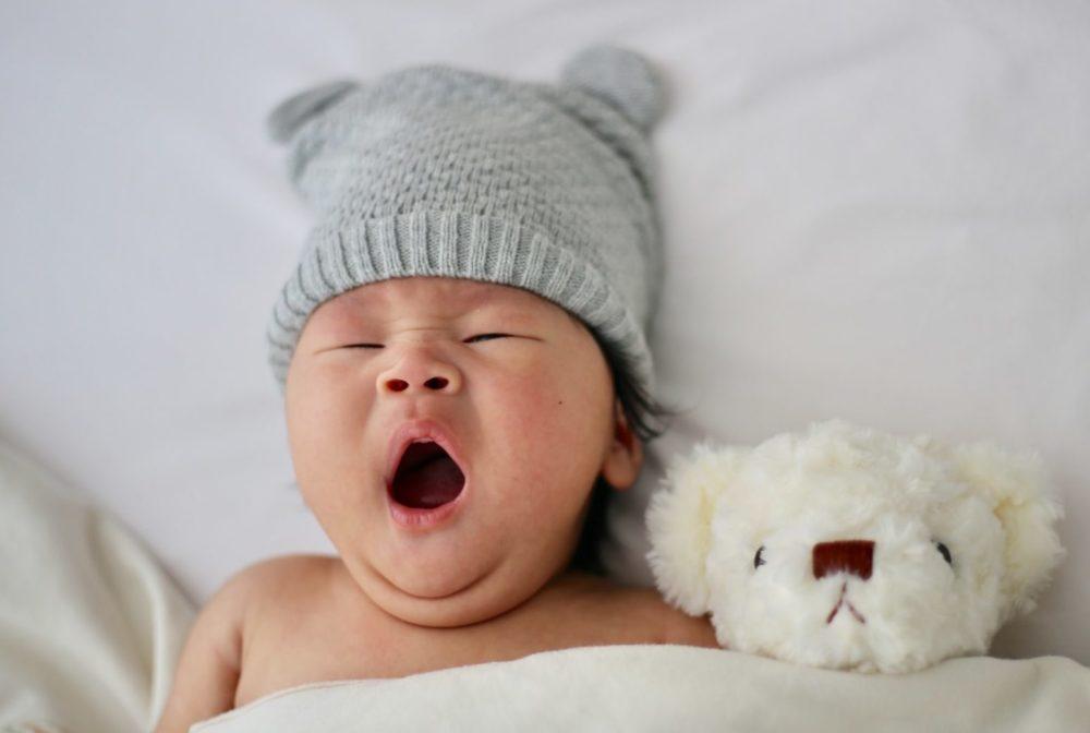Gapende baby in bed met knuffeltje, bovenaanzicht