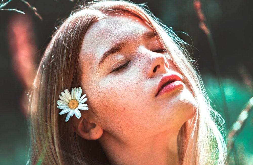 Vrouw met bloem in haar, in de zon. Vooraanzicht, close-up