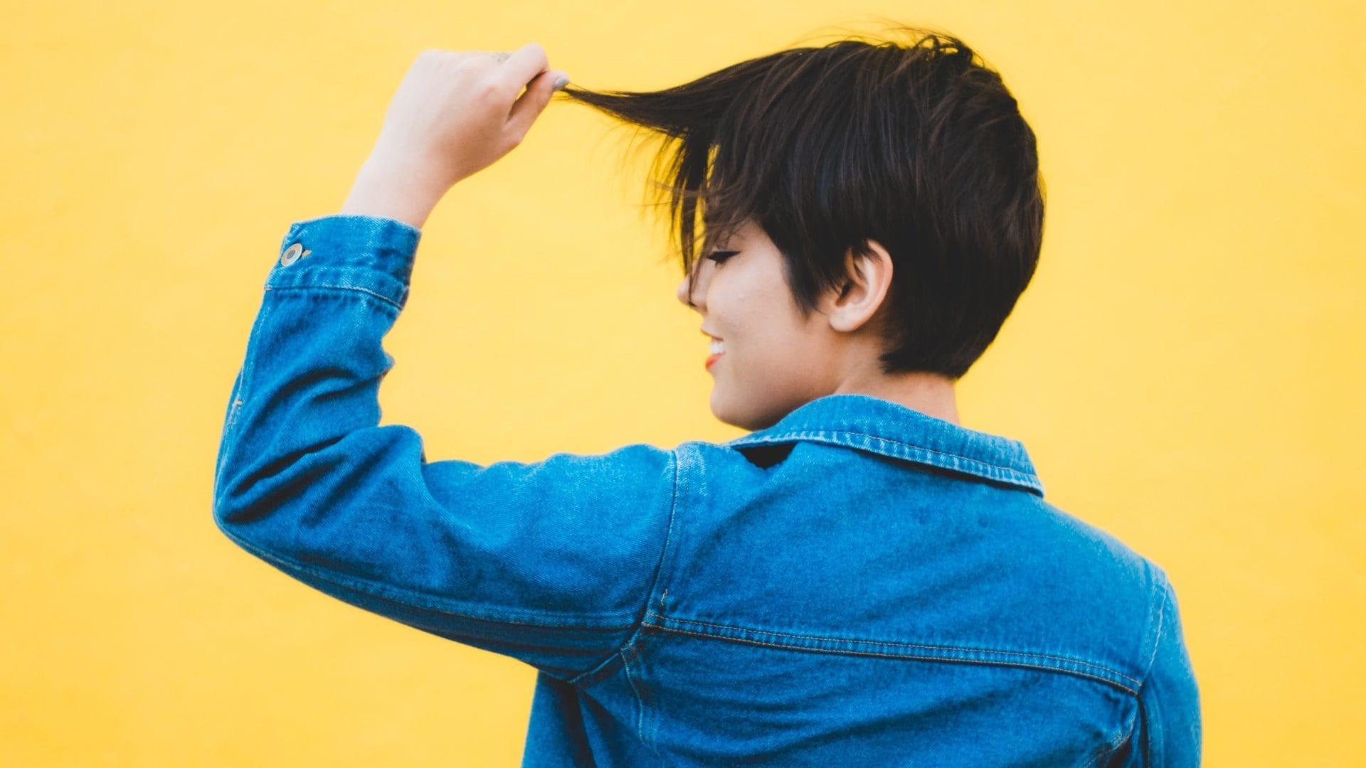 Persoon met kort haar op gele achtergrond. Achterzijde.
