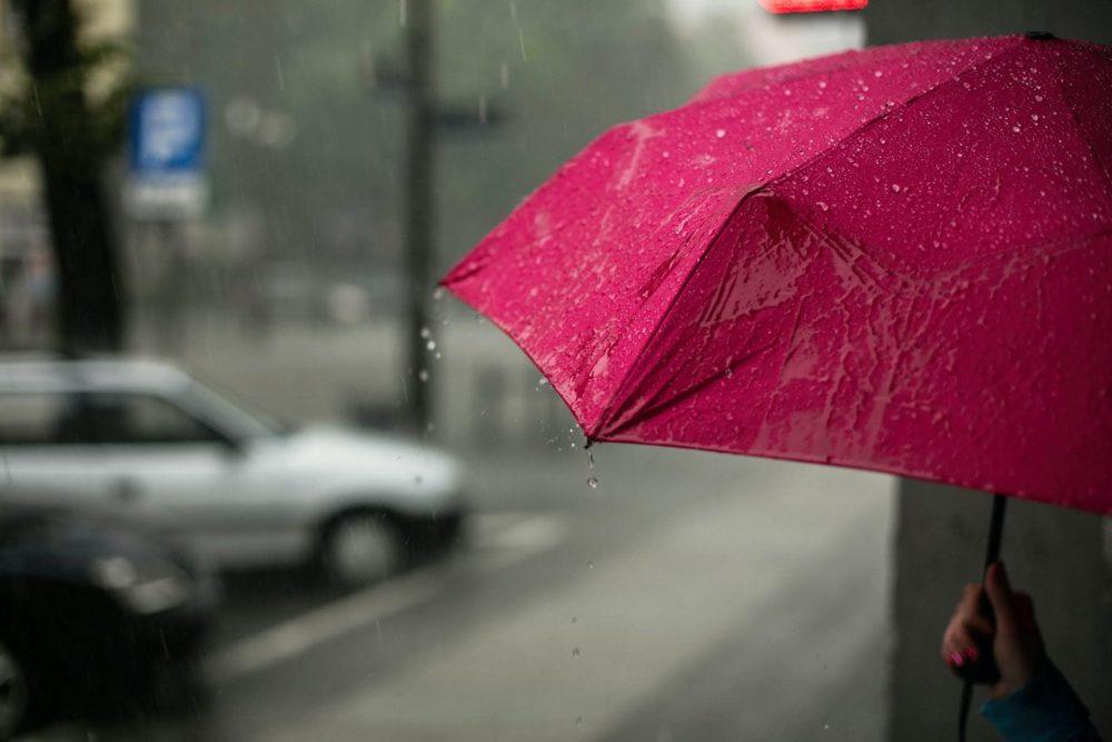 Rode paraplu in de regen met weg en geparkeerde auto op de achtergrond. Zij-aanzicht