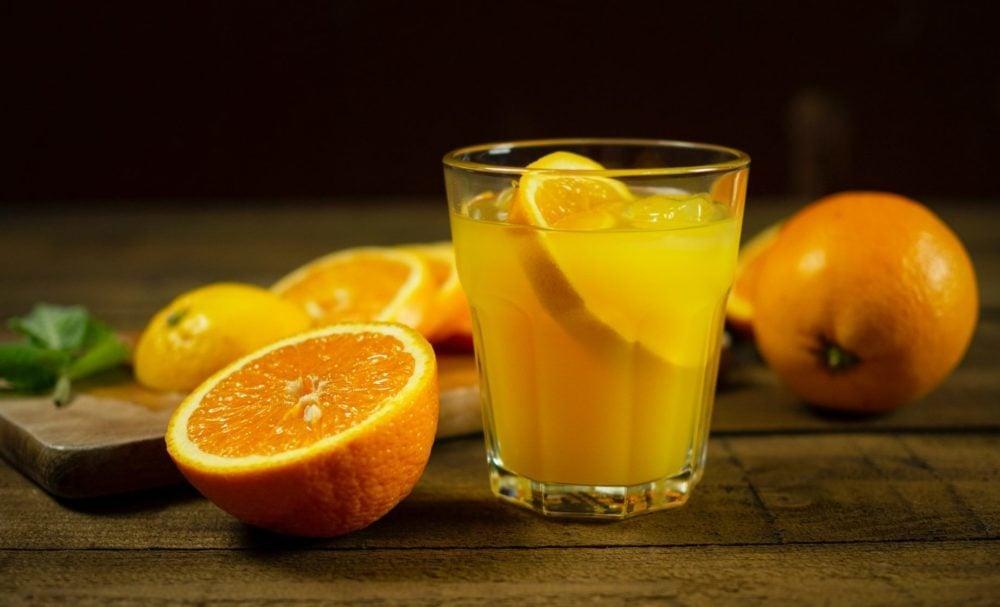 Glas sinaasappelsap met twee sinaasappels