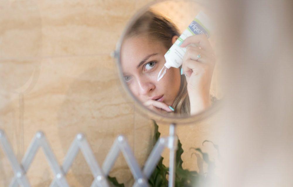 Vrouw die in de spiegel creme aanbrengt. Vooraanzicht.