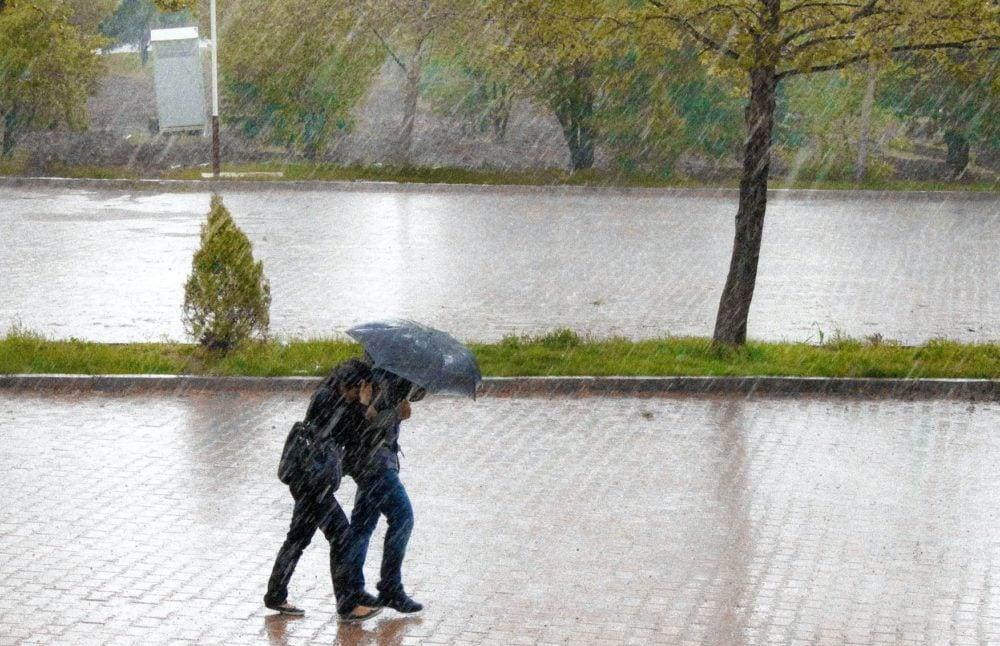 Twee mensen wandelen in de regen, onder de paraplu. Zij-aanzicht