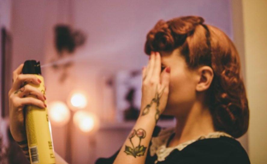 Vrouw die hairspray op haar sprayt, zij-aanzicht