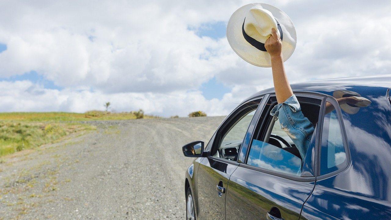 Auto op onverharde weg, iemand zwaait zijn hoed uit het raam. Achterzijde.