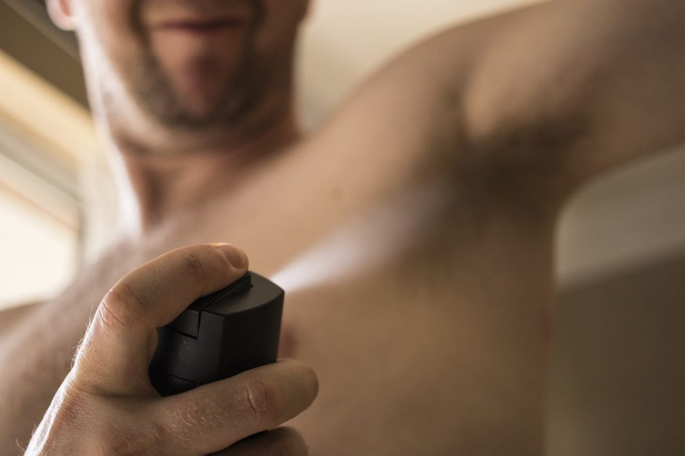 Persoon spuit deodorant onder arm, vooraanzicht
