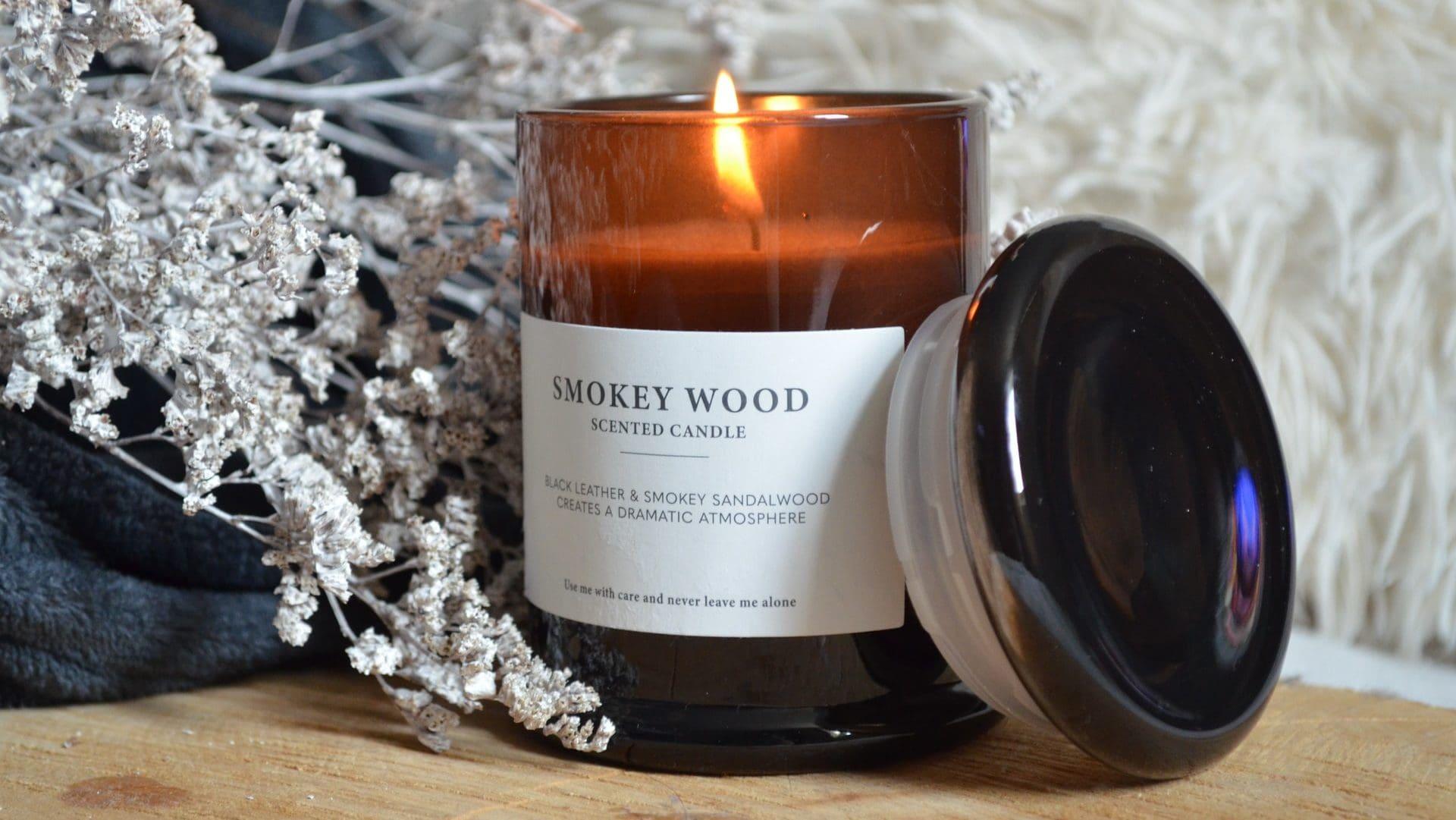 Geurkaars, smokey wood, in glazen pot op houten ondergrond. Vooraanzicht